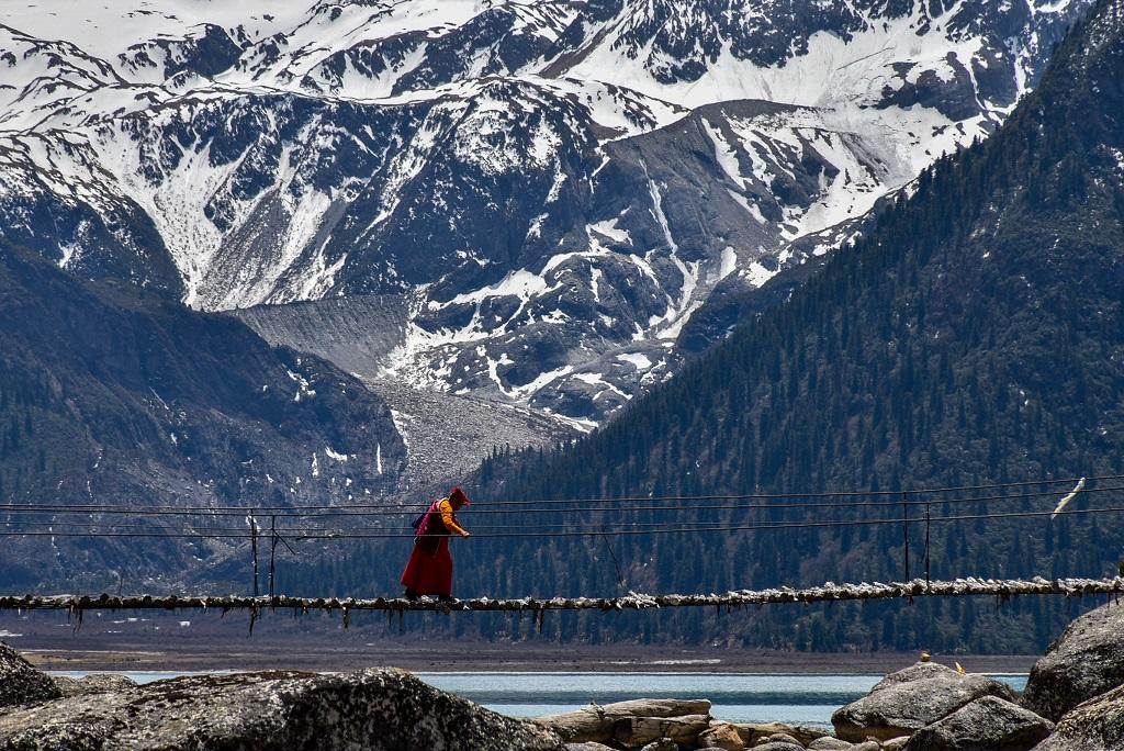 A solitary monk crossing the bridge at Yilhun Lha-Tso